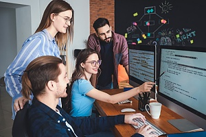 Group of employees looking at computer monitor