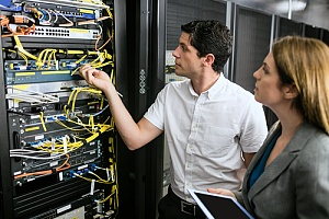 Employees organizing structured network cables in a NYC business server room