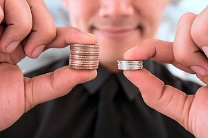 a man holding two stacks of coins to demonstrate higher profits
