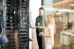 it security worker talking to an office worker about penetration testing next to server racks