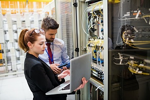 two it security workers in a large server room fixing an issue for a client