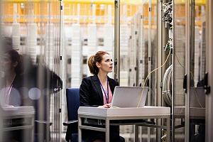 woman sitting at a work station in a server room to perform it security checks