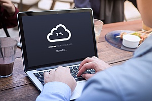 an employee uploading documents to the cloud through data backup services