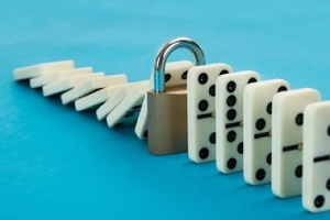 business continuity plan concept with lock and dominos