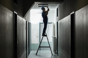 Male Electrician On Step Ladder Installing Light At Corrido