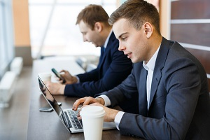 modern it experts with laptop entering business information